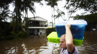Doing what must be done ... Darren Mundie carries possessions from his flooded home in Milton, a suburb of Brisbane.