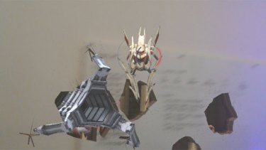 Flying robots burst through the office walls playing Robo Raid with the Hololens headset.