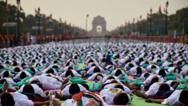 Indian Prime Minister Narednra Modi, center front, lies down on a mat as he performs yoga along with thousands of Indians on Rajpath, in New Delhi, India, Sunday, June 21, 2015. Millions of yoga enthusiasts are bending their bodies in complex postures across India as they take part in a mass yoga program to mark the first International Yoga Day.