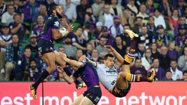 Josh Addo-Carr (left) and Curtis Scott of the Storm and Darius Boyd of the Broncos contest during the first NRL preliminary final.