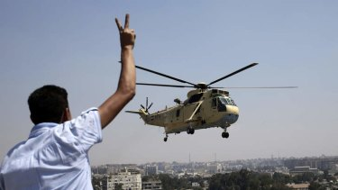 Strong presence: A man flashes a victory sign at an Egyptian military helicopter as it flies over the presidential palace in Cairo.