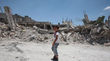 A boy walks past destroyed buildings in the Syrian town of Kobane.