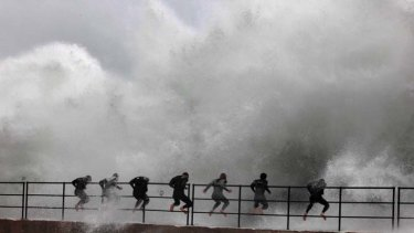 Wall of water warriors ... a group of boys in wet suits take on the rough seas lashing Wollongong Harbour's breakwall. It has been the wettest July in more than 60 years.