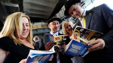 Melbourne Cup punters study the form at Southern Cross Station.