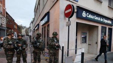 Military conduct patrols in Saint Denis as police conduct terror raids.