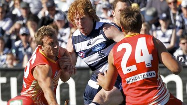 On the boot: Geelong captain Cameron Ling squeezes a kick between Suns midfielders Sam Iles (left) and David Swallow.