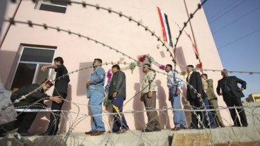 High security ... voters are searched before being allowed into a polling station as dozens of bombs rocked Baghdad yesterday.