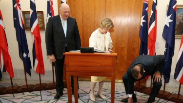 Prime Minister Tony Abbott helps Queen Sonja of Norway pick up a pen at a meeting with King Harald V at Parliament House on Monday.