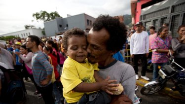 A man kisses his baby during a protest for food in Caracas, Venezuela.