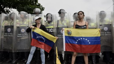 Protesters hold Venezuelan Flags in front of police during an opposition march in Caracas on May 11.