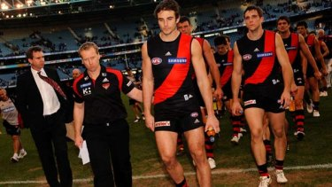Essendon coach Matthew Knights walks off the field with  captain Jobe Watson and team after another loss.