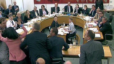 House of Commons Committee members and Rupert Murdoch's wife, Wendi Deng, in pink, react as Jonathan May-Bowles tries to throw a paper plate covered in shaving foam over Mr  Murdoch.