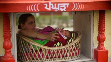 A Red Cross worker collects a baby girl left anonymously at the Red Cross offices in Amritsar, Punjab.