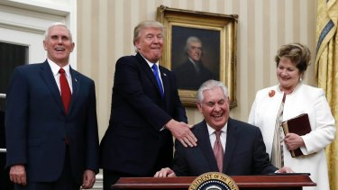 US Secretary of State Rex Tillerson (seated), joined by President Donald Trump, Vice-President Mike Pence (left) and his wife Renda St. Clair, laughs after  being sworn in.