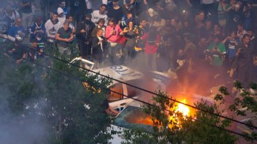 Rioters burn police cars after the Vancouver Canucks were defeated by the Boston Bruins.