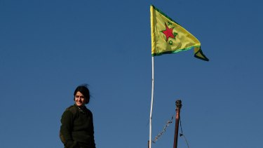 A YPG fighter stands atop a farmhouse near the contested town of Tel Hamis, the yellow YPG flag raised to symbolise the area's liberation from IS.