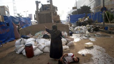 No-go zone: a woman stands between a military bulldozer and a wounded protester near Rabaa al-Adawiya mosque.