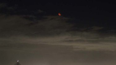 Total lunar eclipse ... the moon glows red over Sydney this morning.
