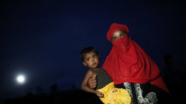 A Rohingya woman holds a child and stands for a photograph at Palangkhali refugee camp in Cox's Bazar, Bangladesh.