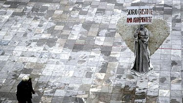 A woman dressed as an angel in a Ciudad Juarez square holds a sign that reads, ''Hitman, Christ loves you, repent.''