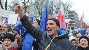 People shout slogans as anti-government protesters gather in front of the Constitutional Court in Warsaw, Poland.