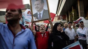 Turkish people hold a picture of Turkish Prime Minister Recep Tayyip Erdogan and flags as they celebrate after Erdogan was on course for a crushing first-round victory in presidential elections