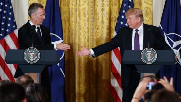 President Donald Trump reaches to shake hands with NATO Secretary General Jens Stoltenberg during a news conference.