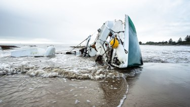 A smashed boat lies on a Devonport beach.