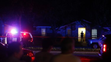Onlookers watch police at the shooting at a home in Plano on Sunday night.