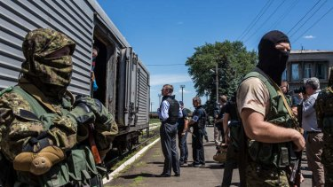 Alexander Hug (centre), Deputy Chief Monitor of the Organisation for Security and Cooperation in Europe (OSCE) Special Monitoring Mission to Ukraine, visits a train containing the bodies of victims of the MH17 crash in Torez, Ukraine as pro-Russia rebels guard the site.