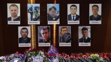 Flower tributes in front of portraits of Russian TV journalists who were killed in the crash.