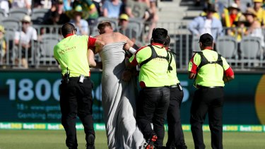 Walk of shame: A streaker is escorted off the ground by security.