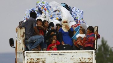 Syrian Kurdish refugees arrive on the back of a truck near the southeastern Turkish town of Suruc