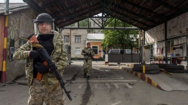Win for separatists ... Pro-Russian militia men walk in an entrance to a border guards base, which they seized, on the outskirts of Luhansk, Ukraine.