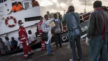 Processing: Refugees from Gambia, Nigeria, Ghana, Bangladesh, Afghanistan and other countries disembark an Italian commercial ship after being rescued at sea.