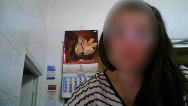 An image uploaded to a hacking forum showing a woman starting at her computer as seen through her webcam.