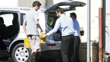Soy long ... a Luxe Bakery Cafe employee helps health officials load cartons of the soy milk into a car.