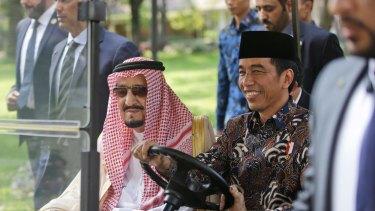 Saudi King Salman, left, rides on a golf cart with Indonesian President Joko Widodo.