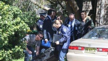 Police carry away evidence after a raid in Marsfield, Sydney on Thursday.