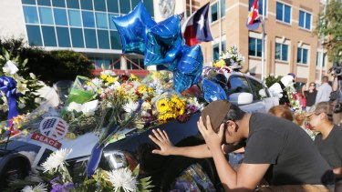 Vicente Alfaro, 15, places his hand on a Dallas police cruiser after leaving a flowers at a makeshift memorial outside Dallas Police Department headquarters.