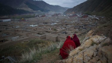 Two monks sit on a hillside overlooking the Labrang monastery in Xiahe, Gansu province, a flashpoint for many Tibetan protests against Chinese authorities.