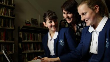 Remy Sica, left, and Sophia Taylor with librarian Stacey Taylor view websites in the school library at Monte Sant' Angelo Mercy College.