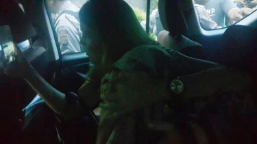 Mercedes Corby shields her sister Schapelle, who has her face covered, in the car taking her to the parole office.