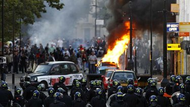 """This is sheer criminality"" ... riot police block a road near a burning car in Hackney."