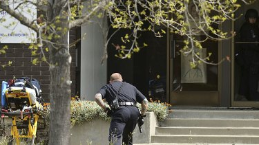 An Oakland police officer approaches the entrance to Oikos University in Oakland, California, where up to seven people have been shot dead