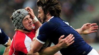 Jonathan Davies of Wales tackles Maxime Medard of France.