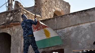 An Iraqi soldier removes a Kurdish flag from Altun Kupri on the outskirts of Irbil, Iraq.