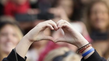 A fan holds her hands in the shape of a heart as Canadian singer Justin Bieber performs.