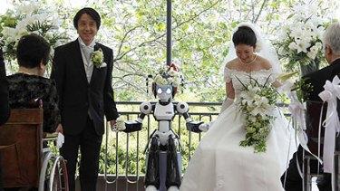 I-Fairy the robot with the bride and groom, Tomohiro Shibata  and Satoko Inoue in Tokyo.