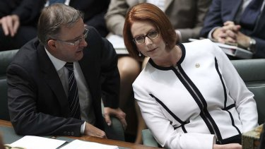 Prime Minister Julia Gillard speaks with Anthony Albanese during question time.